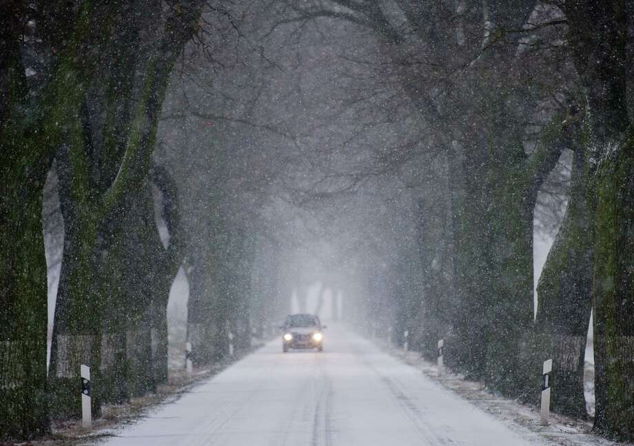 A car drives through snow on an alley near Petersdorf, northern Germany, on December 23, 2012. Temperatures around the freezing point led to icy conditions in northern and eastern parts of Germany.  Photo: PATRICK PLEUL, AFP/Getty Images / DPA
