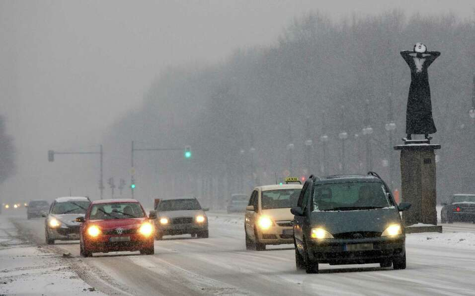 Snow falls while cars drive in Berlin, Germany, on Dec. 23, 2012.