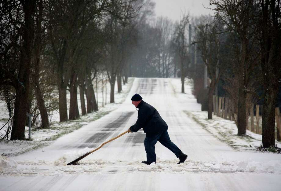 A man clears a street off snow on December 23, 2012, in Rosenow, northern Germany. Photo: JENS BUTTNER, AFP/Getty Images / DPA
