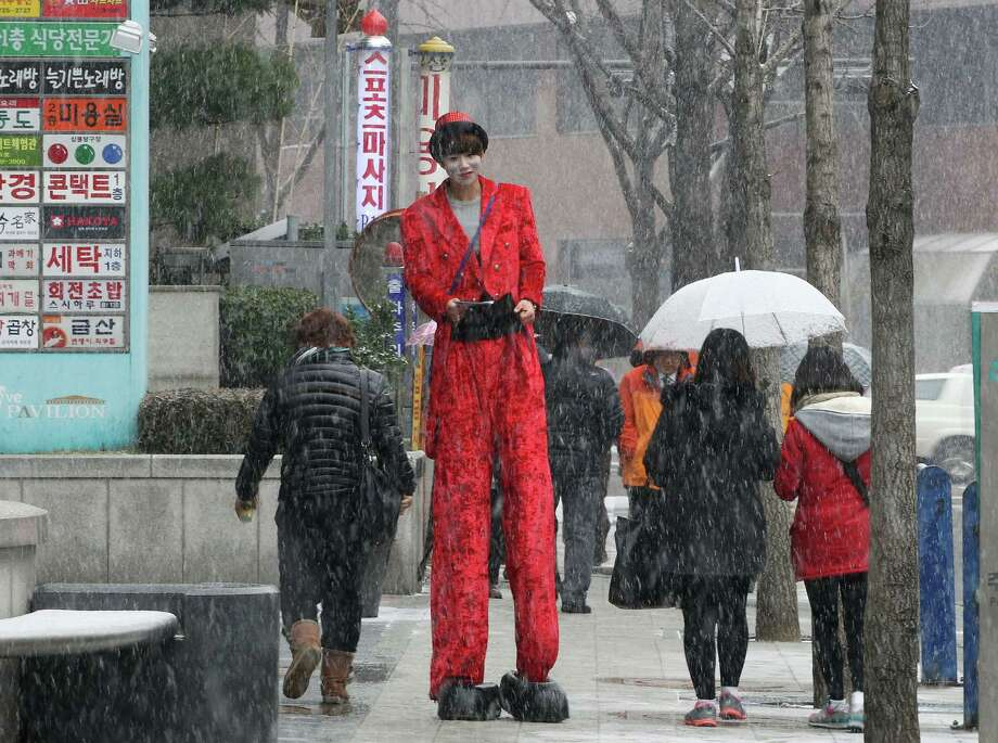 A street clown distributes flyers promoting a coffee bar to passers-by in the snow in Seoul, South Korea, Friday, Dec. 21, 2012. The temperature in Seoul reached minus 3 degree Celsius (26 degree Fahrenheit) in the morning. Photo: Ahn Young-joon, Associated Press / AP