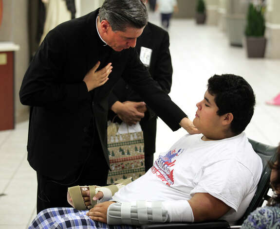 San Antonio Archbishop Gustavo García-Siller visits with Gilbert Rangel who will be in Christus Santa Rosa Children's Hospital of San Antonio over Chrisitmas on Dec. 24, 2012. Photo: Bob Owen, San Antonio Express-News / © 2012 San Antonio Express-News