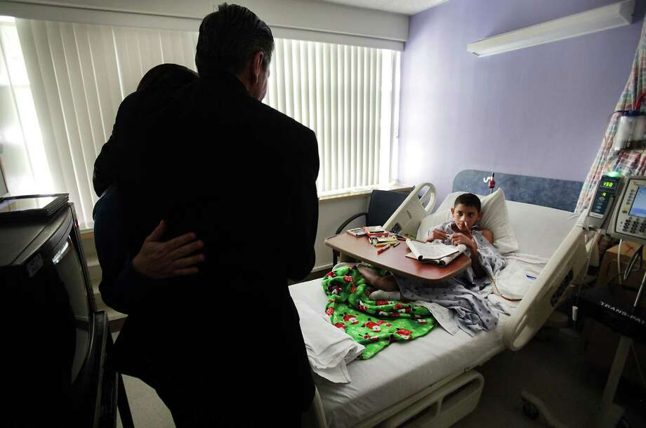 San Antonio Archbishop Gustavo García-Siller hugs Rosalinda Martinez as the Archbishop visits her son, Juan Antonio Martinez, and other children who will be in Christus Santa Rosa Children's Hospital of San Antonio over Christmas, om Dec. 24, 2012. Photo: Bob Owen, San Antonio Express-News / © 2012 San Antonio Express-News