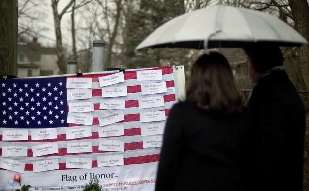 Mourners looks at the names on a U.S. flag of the Sandy Hook Elementary School shooting victims at a sidewalk memorial, Sunday, Dec. 16, 2012, in Newtown, Conn.A gunman walked into Sandy Hook Elementary School in Newtown Friday and opened fire, killing 26 people, including 20 children.  (AP Photo/David Goldman) Photo: David Goldman