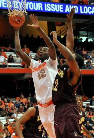 In this Nov. 4, 2012 photo, Syracuse's Baye Moussa Keita (12) scores against Bloomsburg during the second half of an NCAA college exhibition basketball game in Syracuse, N.Y. Keita is from Africa, as is Syracuse football player Siriki Diabate. Soccer, once the mainstay of their lives, is now an afterthought at best. (AP Photo/Kevin Rivoli) Photo: Kevin Rivoli