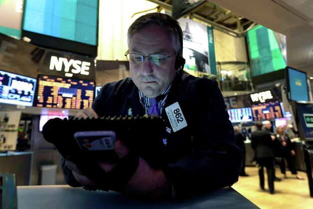 FILE - In this New York Stock Exchange Friday, Dec. 21, 2012, photo, Trader Warren Meyers uses his handheld device as he works on the floor of the New York Stock Exchange. Stocks are down Monday, Dec. 24, 2012, amid concern that lawmakers will fail to reach a deal to stop the U.S. going over the so-called fiscal cliff. (AP Photo/Richard Drew) Photo: Richard Drew