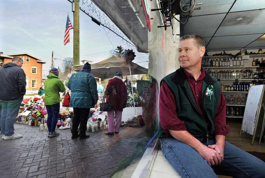 Mike Kerler, owner of Sandy Hook Wine and Liquer looks at the window of his store Monday, Dec. 24, 2012. Memorials to the victims of the Sandy Hook Elementary School are set up right outside his shop door. Photo: Carol Kaliff / The News-Times