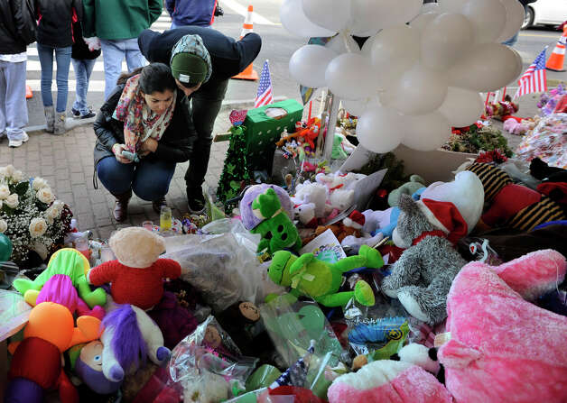 Makeshift memorials to the victims of the Sandy Hook Elementary School shootings draw vistors to Newtown. This one is in the center of Sandy Hook, Monday, Dec. 24, 2012. Photo: Carol Kaliff / The News-Times