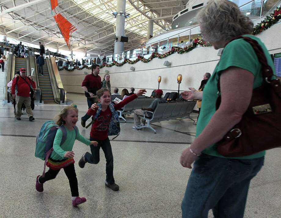 Four-year-old Chloe Ladner lower left, and her seven-year-old sister Maddie Ladner center run to greet their grandmother Debbie Dykstra right, after arriving on a flight from Pennsylvania at Hobby Airport Monday, Dec. 24, 2012, in Houston. Photo: James Nielsen, Chronicle / © Houston Chronicle 2012