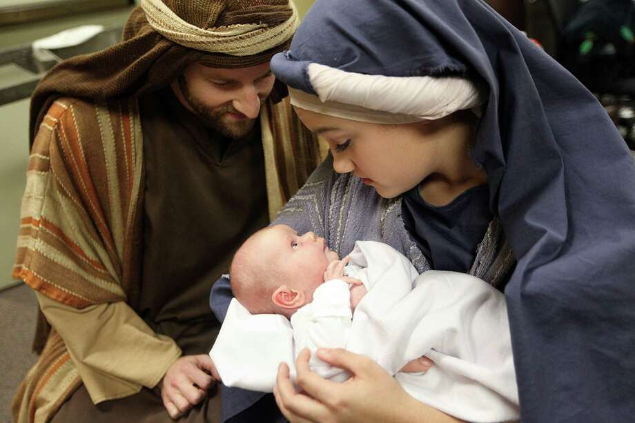 """David Saxe as """"Joseph"""", Caroline Taylor as """"Mary"""", 16, holds Rachel Hudson as """"Baby Jesus"""" during the Christmas Eve Candlelight Service at Houston's First Baptist Church on Monday, Dec. 24, 2012, in Houston. Photo: Mayra Beltran, Houston Chronicle / © 2012 Houston Chronicle"""