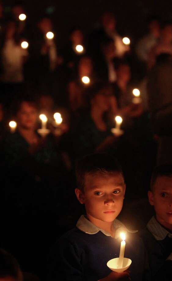 Gavin Ott, 8, listens to the congregation sing Silent Night, Holy Night during the Christmas Eve Candlelight Service at Houston's First Baptist Church on Monday, Dec. 24, 2012, in Houston. Photo: Mayra Beltran, Houston Chronicle / © 2012 Houston Chronicle