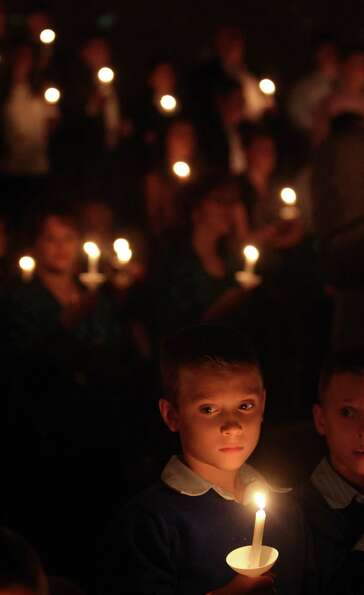 Gavin Ott, 8, listens to the congregation sing Silent Night, Holy Night during the Christmas Eve Can