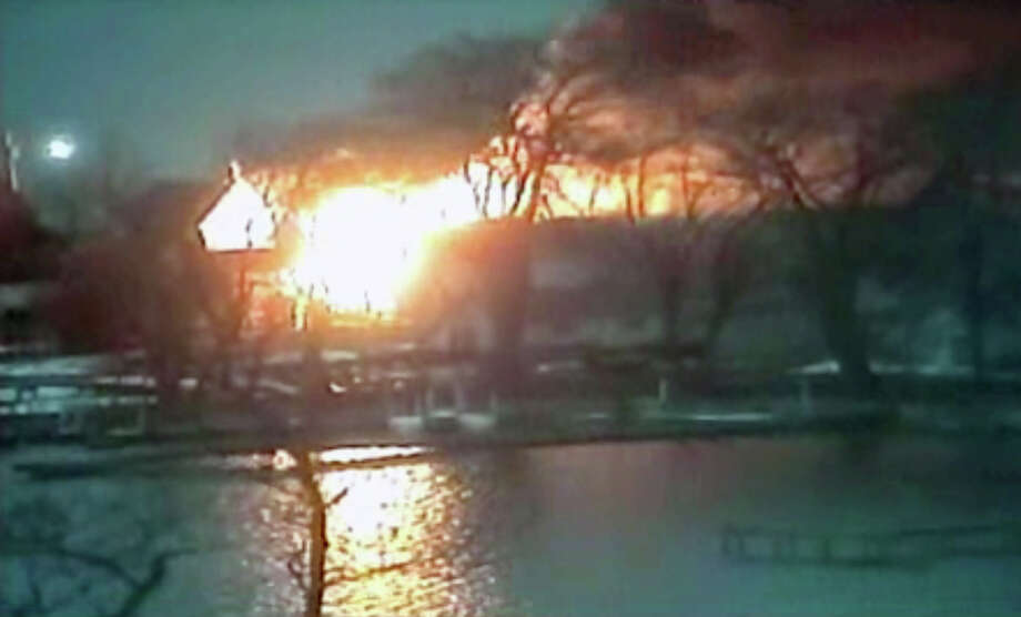 This image taken from video provided by WHAM13-TV, shows a wide view of homes on fire in an area where a gunman ambushed four volunteer firefighters responding to an intense pre-dawn house fire early Monday, Dec. 24, 2012, in Webster, N.Y., killing two before ending up dead himself, authorities said. Police used an armored vehicle to evacuate more than 30 nearby residents. (AP Photo/WHAM13-TV via AP video) Photo: Uncredited