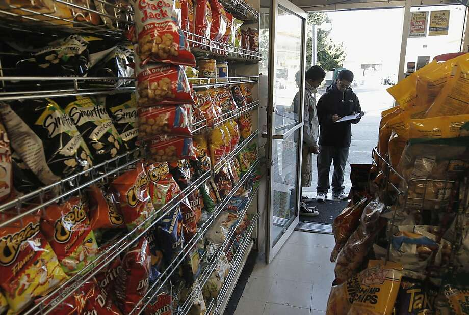 Chips and snacks line racks near the door, where Zakariaya Shaikh (right) asks Charles Ollie about what he buys. Photo: Michael Macor, The Chronicle
