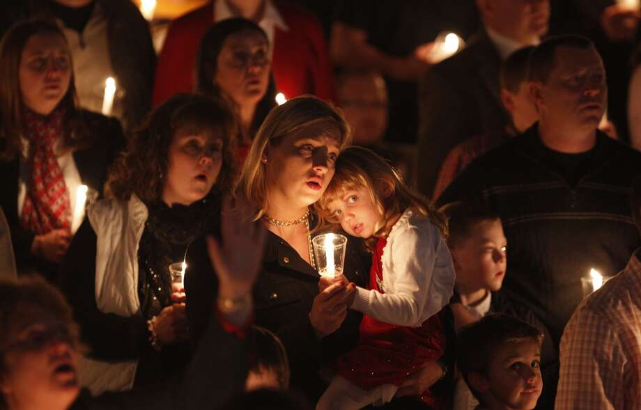 Christian worshippers hold candles at a service in Getzville, N.Y.