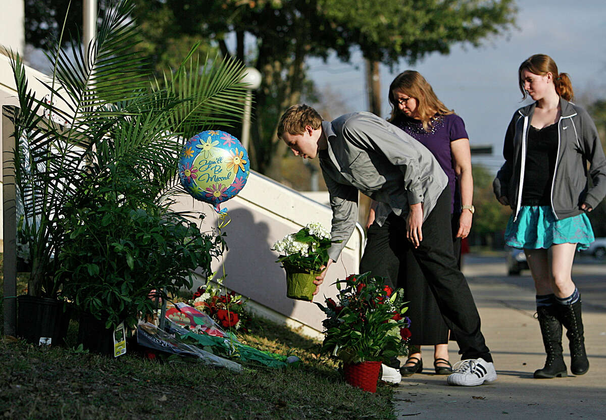 Steven Hester, 18, places flowers at a memorial for slain police officer Jimmie Norman on Monday outside the Bellaire Police and Courts Building. Hester is joined by his sister Jess, right, and mother, Linda.