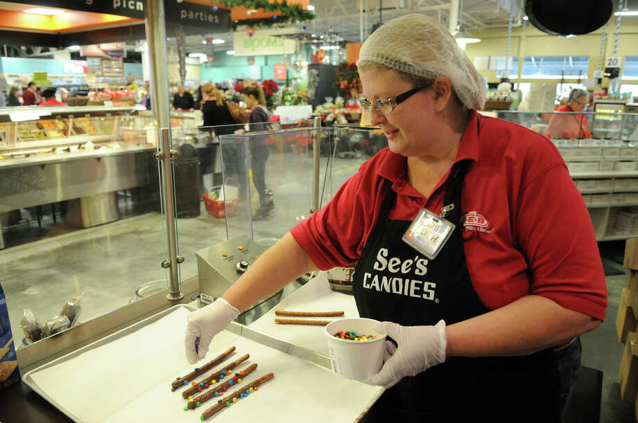 Judith Andersen of Conroe works on milk chocolate pretzel rods with M&M's at the See's Candies shop at the H-E-B Woodlands Market Street. The candy store concept opened last year. Photo: Jerry Baker, Freelance