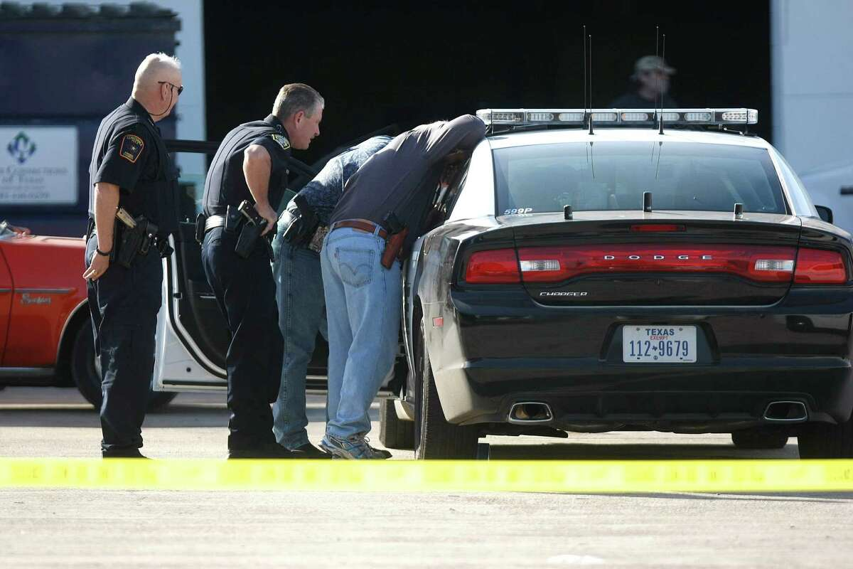 Police work the crime scene outside a Maaco body shop on Monday after a Bellaire police officer and the shop owner were shot to death.