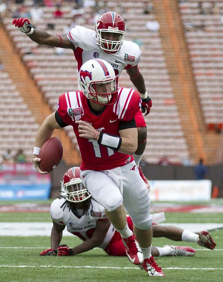 SMU quarterback Garrett Gilbert runs past two defenders for a second-quarter touchdown. Photo: Eugene Tanner, Associated Press