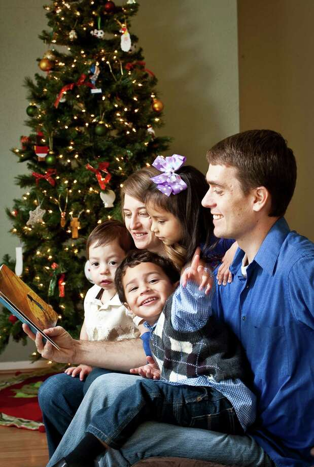 Beth Gould, center, and her husband Tim Gould, right, read with their children Isiah, 1, left, Daniel, 2, right, and Lilyana, 4, Saturday, Dec. 22, 2012,  in Pearland. This will be the first Christmas the family will spend together, the children were adopted a week ago. ( Nick de la Torre / Houston Chronicle ) Photo: Nick De La Torre, Staff / © 2012  Houston Chronicle