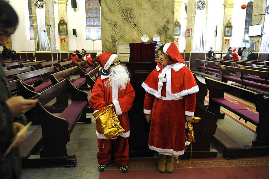 This picture taken on December 24, 2012 shows a Chinese boy (L) and a girl (R) dressed as Santa Claus chatting before the Christmas Eve mass at a Catholic church in Beijing. While China does not officially celebrate Christmas, its popularity continues to grow with non-Christians keen to see and feel the experience of Christmas.    AFP PHOTO / WANG ZHAOWANG ZHAO/AFP/Getty Images Photo: Wang Zhao, AFP/Getty Images