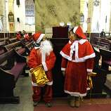 This picture taken on December 24, 2012 shows a Chinese boy (L) and a girl (R) dressed as Santa Claus chatting before the Christmas Eve mass at a Catholic church in Beijing. While China does not officially celebrate Christmas, its popularity continues to grow with non-Christians keen to see and feel the experience of Christmas.    AFP PHOTO / WANG ZHAOWANG ZHAO/AFP/Getty Images