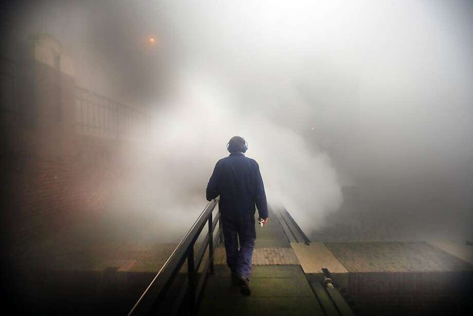 A man walks on a platform as steam rises from the boilers of a pumping-station in Lemmer, the northern Netherlands, on December 24, 2012. The station pumps excess water from the northern province to a nearby lake. The authorities decided to turn on the pumping-station due to expected heavy rainfall. AFP PHOTO / ANP / CATRINUS VAN DER VEEN   ***Netherlands out***CATRINUS VAN DER VEEN/AFP/Getty Images Photo: Catrinus Van Der Veen, AFP/Getty Images