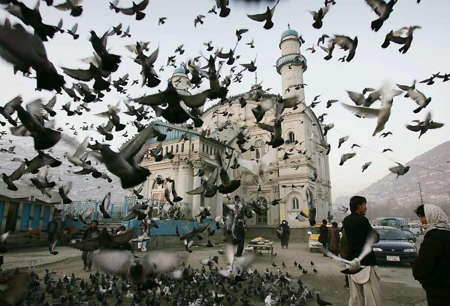 Pigeons fly outside Shah-e-Doshamshera's mosque in Kabul, Afghanistan, Monday, Dec. 24, 2012. (AP Photo/Ahmad Nazar) Photo: Ahmad Nazar, Associated Press