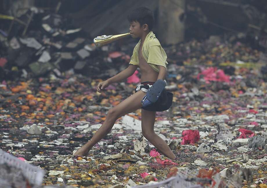 A Filipino boy blows a paper trumpet as he wades along a bed of soiled fruits and debris after fire broke at a commercial establishment at the busy shopping area of Divisoria, in Manila, Philippines on Christmas eve, Monday Dec. 24, 2012. Many Filipinos do their holiday shopping in the area because of cheap prices. Investigators are still determining the cause of the fire. (AP Photo/Aaron Favila) Photo: Aaron Favila, Associated Press