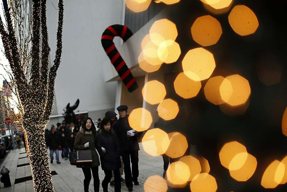 Holiday shoppers walk past a large candy cane Christmas decoration hanging from the side of the Solow Building in New York, U.S., on Sunday, Dec. 23, 2012. Holiday shoppers descended on U.S. stores this weekend in a last-minute dash to buy gifts amid concerns about the nation's economy and the impasse in Washington over taxes and spending. Photographer: Victor J. Blue/Bloomberg Photo: Victor J. Blue, Bloomberg