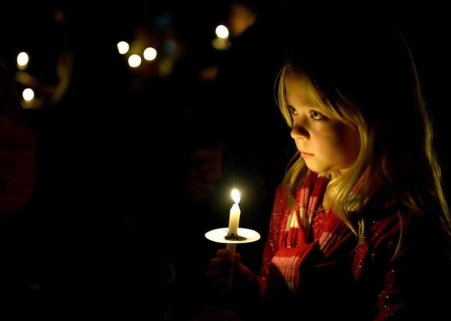 Faith Hartlaub, 7, of Aliso Viejo takes part in a candle lighting service at the end of Coast Hills Church's Christmas Eve service in Aliso Viejo Monday DEC. 24, 2012. Christmas Eve services featured live music, dance, videography and the special effects drizzle of snow. There was also a live nativity scene outside the church with two miniature horses, a goat three chickens and several high school students. About 4,000 people were expected to attended the services. (AP Photo/Orange County Register, Mindy Schauer) MANDATORY CREDIT Photo: Mindy Schauer,, Associated Press