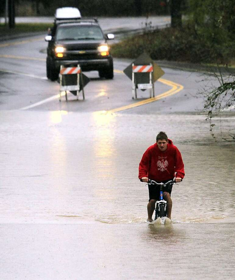 File--In this Jan. 20, 2012, file photo Oregon State student Blair Davis bikes through several feet of floodwaters in Corvallis, Ore.  Heavy statewide flooding early in the year is one of Oregon's top 2012 stories.(AP Photo/Don Ryan, file) Photo: Don Ryan, Associated Press