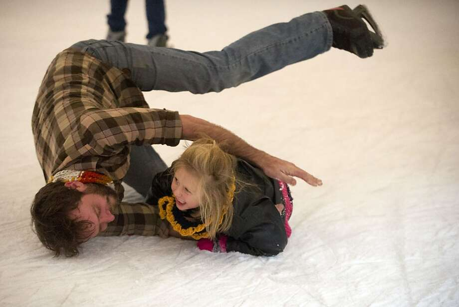 "Violet Epperson-Scott, 5, and her father Ben Epperson laugh as they fall to the ice while skiing at Holidays on Ice on Market Square in Knoxville, Tenn., on Sunday, Dec. 23, 2012. ""We've specifically came out to ice skate,"" said Epperson of his two daughters. ""This is their first time. They did really well. We fell a little bit."" (AP Photo/The Knoxville News Sentinel, Saul Young) Photo: Saul Young, Associated Press"