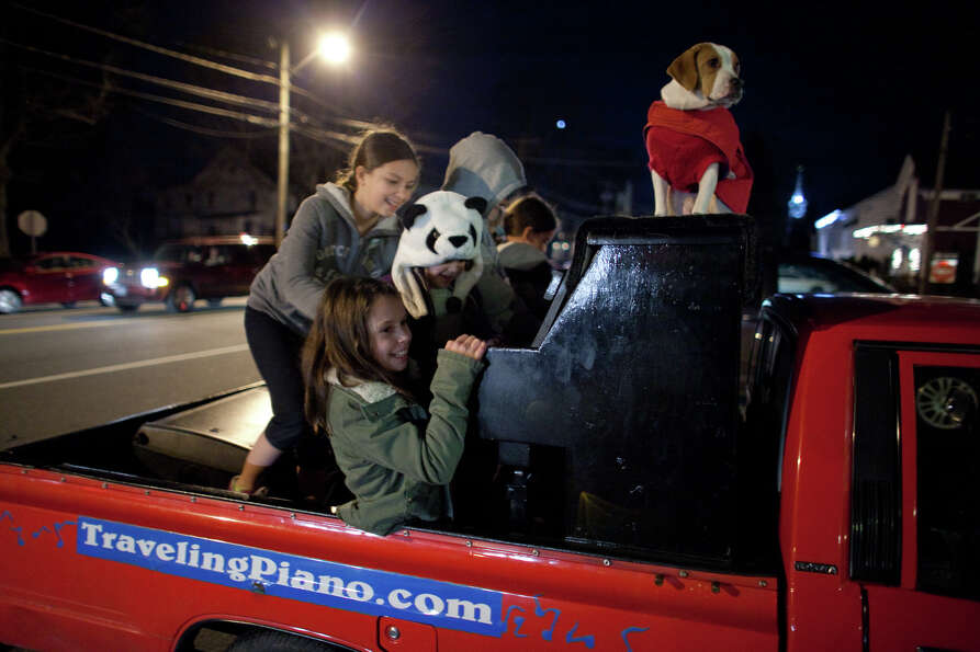 Newtown children gather in the back of the pickup carrying a piano —and a Mo the dog— on Sunday,