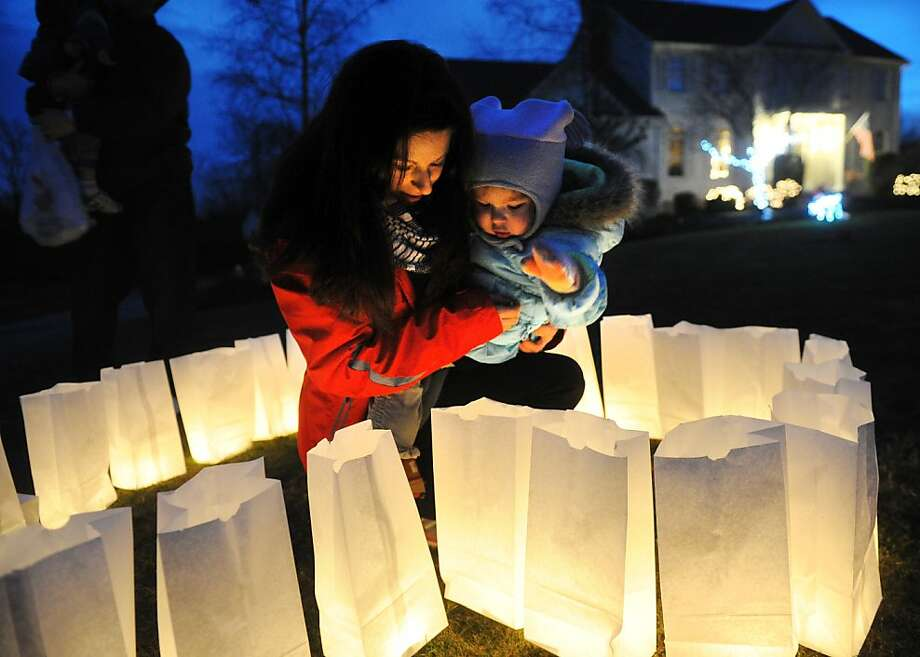 Holly Wheway shows her daughter Esme, 2, luminarias lit in memory of the Sandy Hook Elementary shooting victims in front of her Charter Ridge home in Newtown on Monday, December 24, 2012. The luminaria bags were distributed free to residents at several town retailers. Wheway and her husband, Earl, arranged the lights in the shape of a heart. Photo: Brian A. Pounds