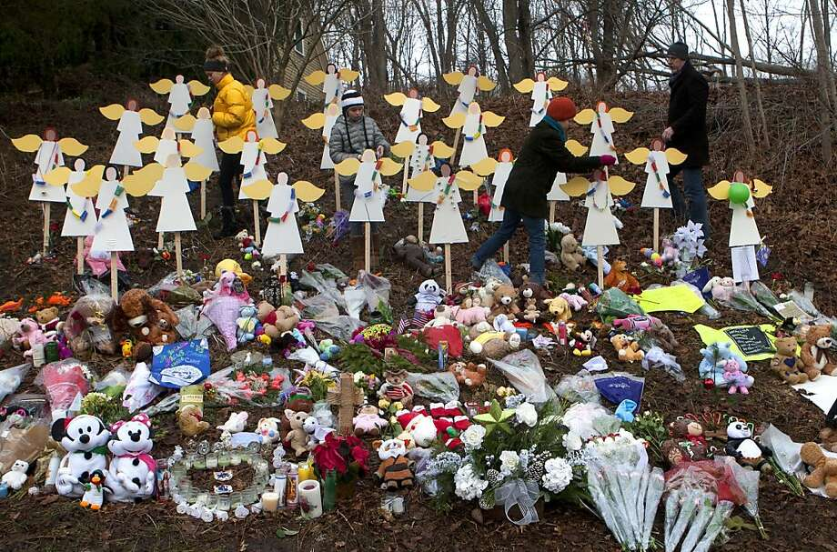 Georgia Hendren, left, Reilly Hendren, along with their mother, Jennifer Hendren, and father Jim Hendren, place prayer flags from Nepal on angels at a memorial site Saturday, Dec. 22, 2012, honoring the 26 who were killed at Sandy Hook Elementary School in Newtown Friday, December 14. The school was evacuated after Adam Lanza opened fire killing 26 individuals, 20 whom were children. ( Cody Duty / Hearst Newspapers ) Photo: Cody Duty, Cody Duty/Hearst Newspapers