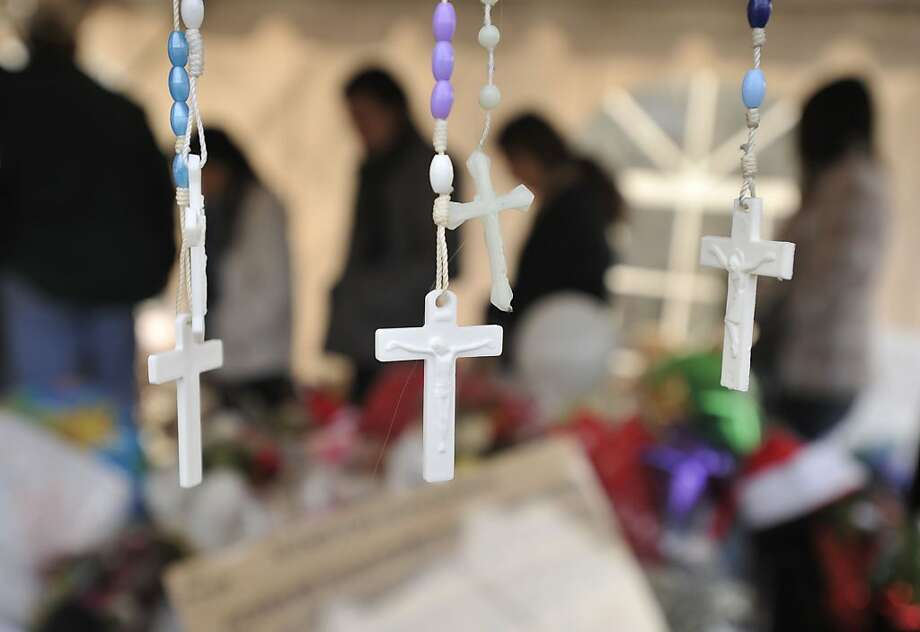 Rosaries hang off a cross among the many makeshift memorials in the downtown Sandy Hook section of Newtown on Monday, Dec. 24, 2012. Photo: Jason Rearick