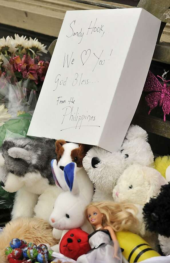 "A makeshift memorial occupies a bench in front of a business in the Sandy Hook section of Newtown on Monday, Dec. 24, 2012. The sign reads, ""Sandy Hook, We Love You! God Bless... From the Phillippines"" Photo: Jason Rearick"