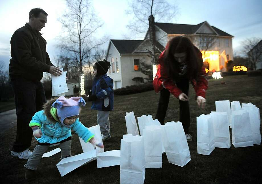 Earl and Holly Wheway and their children Jackson, 4, and Esme, 2, light luminarias in memory of the Sandy Hook Elementary shooting victims in front of their Charter Ridge home in Newtown on Monday, December 24, 2012. The luminaria bags were distributed free to residents at several town retailers. The Wheways arranged the lights in the shape of a heart. Photo: Brian A. Pounds