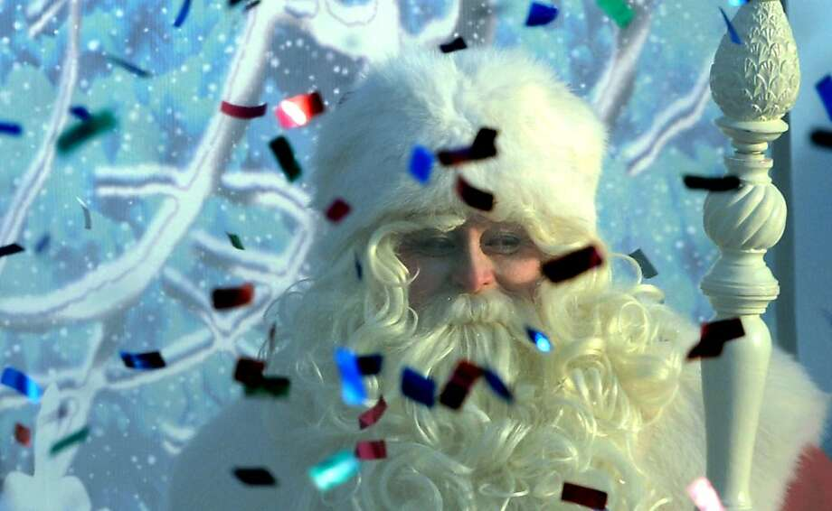 An actor dressed as Ded Moroz (Grandfather Frost), the Russian Santa Claus, smiles through smoke from a fire cracker and flying confetti during a welcome ceremony for him in Moscow's Gorky Park, on December 24, 2012. New Year's is the biggest holiday of the year in Russia, and is followed by the Orthodox Christmas on January 7. AFP PHOTO / KIRILL KUDRYAVTSEVKIRILL KUDRYAVTSEV/AFP/Getty Images Photo: Kirill Kudryavtsev, AFP/Getty Images