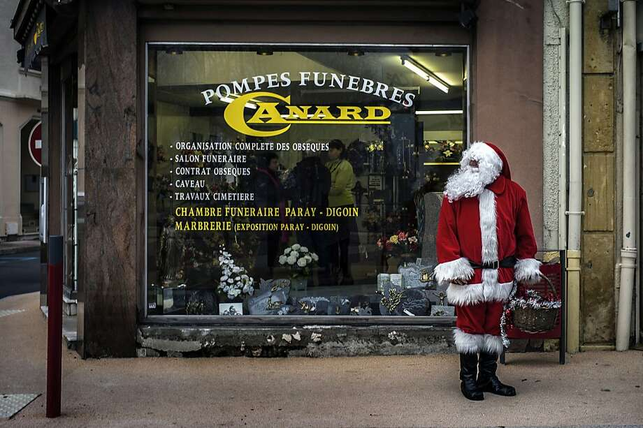 A man dressed as Santa Claus stands in front of a funeral home on December 24, 2012 in Gueugnon.    AFP PHOTO / JEFF PACHOUDJEFF PACHOUD/AFP/Getty Images Photo: Jeff Pachoud, AFP/Getty Images