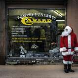 A man dressed as Santa Claus stands in front of a funeral home on December 24, 2012 in Gueugnon.    AFP PHOTO / JEFF PACHOUDJEFF PACHOUD/AFP/Getty Images