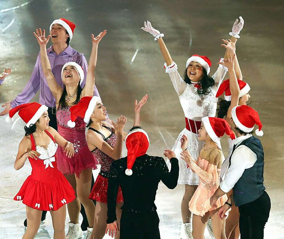 This picture taken on December 24, 2012 shows Japan's top figure skaters dressed in Santa Claus costumes performing at an exhibition after the Japan Figure Skating Championships in Sapporo. Mao Asada won the women's singles and Yuzuru Hanyu won the men's singles of the championships. AFP PHOTO / JIJI PRESS    JAPAN OUTJIJI PRESS/AFP/Getty Images Photo: Jiji Press, AFP/Getty Images