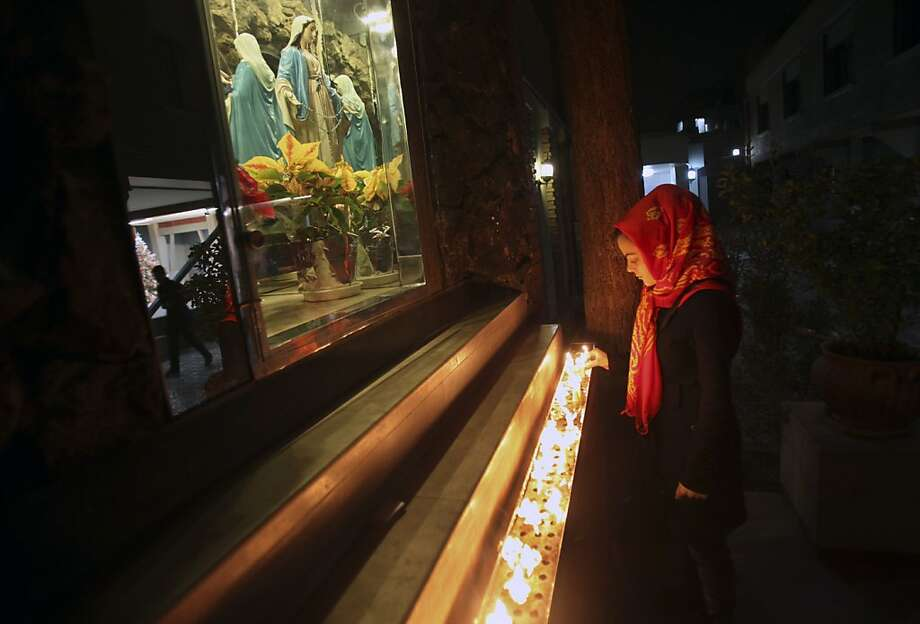 A female Iranian Christian lights candle at the Saint Mary Chaldean- Assyrian Catholic church, on the Christmas eve, in downtown Tehran, Iran, Monday, Dec. 24, 2012. Iran's constitution gives protected status to Christians, Jews and Zoroastrians, but many religious minorities sense growing pressures from the Islamic state. Iran has claimed as a point of pride that it makes space for other religions. It reserves parliament seats for Jewish and Christian lawmakers and permits churches, Roman Catholic, Armenian Orthodox and others, as well as synagogues and Zoroastrian temples that are under sporadic watch by authorities. Religious celebrations are allowed, but no political messages or overtones are tolerated. In past years, authorities have staged arrests on Christians and other religious minorities. (AP Photo/Vahid Salemi) Photo: Vahid Salemi, Associated Press