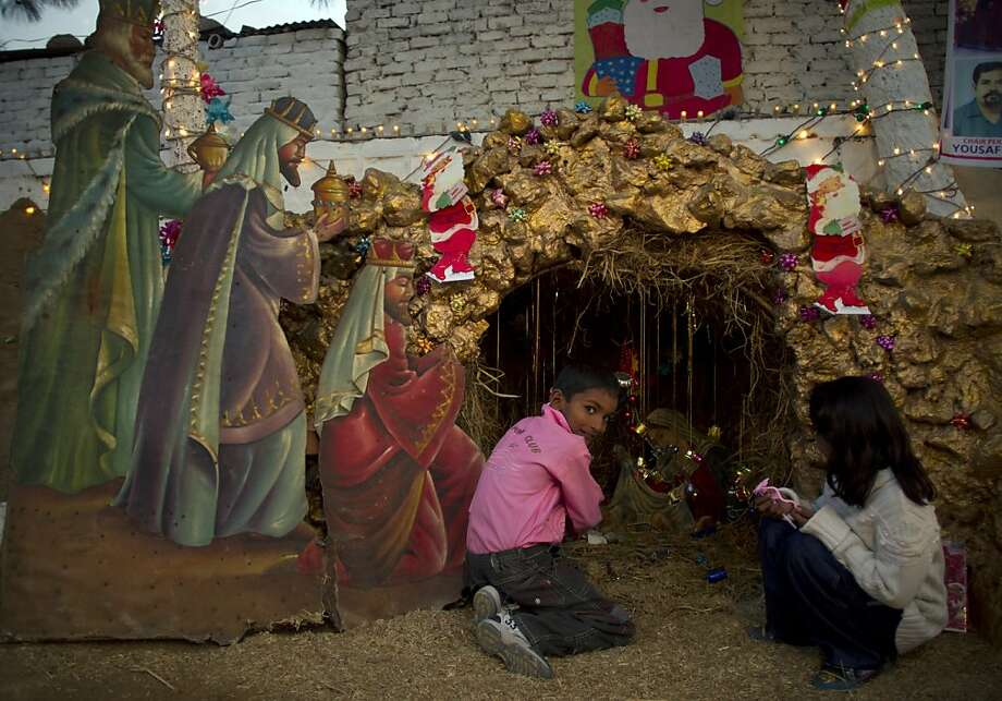 Pakistani Christian children sit by a scene of the nativity, in the slums of Islamabad, Pakistan on Christmas eve, Monday Dec. 24, 2012. Christians are the largest minority community in Pakistan. They constitute about 1.6% of the Pakistan's population, Christmas is a holiday and is observed across the country as an occasion to celebrate. (AP Photo/B.K. Bangash) Photo: B.K. Bangash, Associated Press