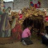 Pakistani Christian children sit by a scene of the nativity, in the slums of Islamabad, Pakistan on Christmas eve, Monday Dec. 24, 2012. Christians are the largest minority community in Pakistan. They constitute about 1.6% of the Pakistan's population, Christmas is a holiday and is observed across the country as an occasion to celebrate. (AP Photo/B.K. Bangash)