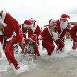 People dressed up as Santa Claus enjoy a traditional Christmas bath on December 23, 2012 in Monaco. AFP PHOTO / VALERY HACHEVALERY HACHE/AFP/Getty Images