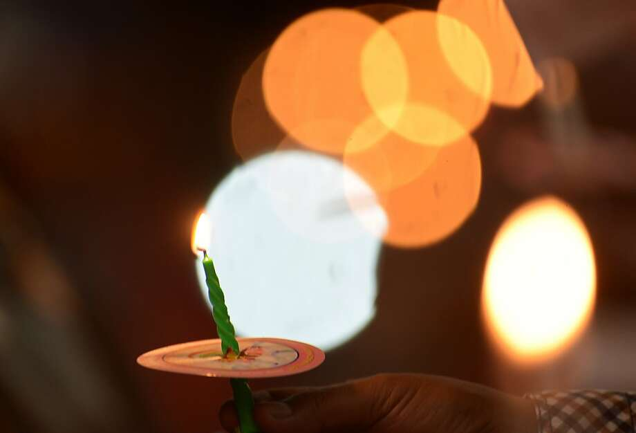 A worshipper holds a candle during Christmas services in Jakarta on Christmas Eve, December 24, 2012. Christians in Indonesia, which comprise about ten percent of the world's largest Muslim-majority nation, celebrated Christmas. AFP PHOTO / ADEK BERRYADEK BERRY/AFP/Getty Images Photo: Adek Berry, AFP/Getty Images