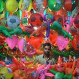 An Indian vendor waits for costumers at a balloon stall during a Christmas fair in Dimapur, India's northeastern state of Nagaland, on Christmas Eve, December 24, 2012. Despite Christians forming a little over 2 percent of the billion plus population in India, with Hindus comprising the majority, Christmas is celebrated with much fanfare and zeal throughout the country. AFP PHOTO/STR STRDEL/AFP/Getty Images