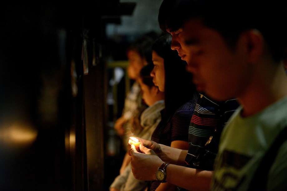 Filipino Christians light candles during a Christmas Eve mass at the Saint Peter Parish in Manila on December 24, 2012. The Philippines is Asia's bastion of Catholicism and has the longest known Christmas season in the region beginning with the dawn masses in mid-December until the first week of January. AFP PHOTO/NOEL CELISNOEL CELIS/AFP/Getty Images Photo: Noel Celis, AFP/Getty Images