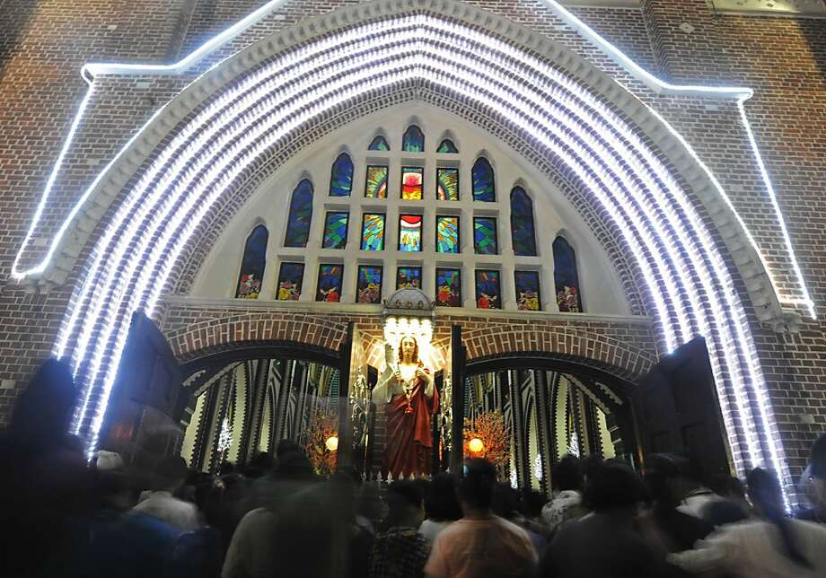 Christrians arrive at St Mary's cathedral for a prayer during the Christmas eve celeberation in Yangon on December 24, 2012. AFP PHOTO / SOE THAN WINSoe Than WIN/AFP/Getty Images Photo: Soe Than Win, AFP/Getty Images